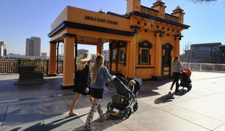 FILE - In this Jan. 17, 2017, file photo visitors walk past Angels Flight Railway in Los Angeles. The tiny funicular that hauled people 298 feet up and down the city's steep Bunker Hill was shut down in 2013 after a series of safety problems. At a news conference Wednesday, March 1, Los Angeles Mayor Eric Garcetti said those issues are being resolved and the railroad's antique wooden cars should be back in service by Labor Day. (AP Photo/Richard Vogel, File)