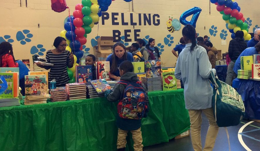 "KPMG employee volunteers and officials from First Book doled out free books to more than 450 children Thursday at the ""Read to Succeed"" book fair, which aims to boost childhood literacy. (Julia Brouillette/The Washington Times)"