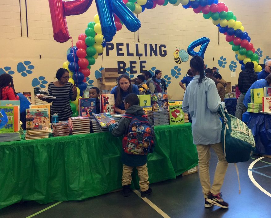 """KPMG employee volunteers and officials from First Book doled out free books to more than 450 children Thursday at the """"Read to Succeed"""" book fair, which aims to boost childhood literacy. (Julia Brouillette/The Washington Times)"""