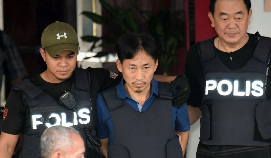 North Korean Ri Jong-chol, center, who was arrested in connection with the death of Kim Jong-un's half-brother, is transferred from Sepang district police station in Sepang, Malaysia on Friday, March 3, 2017. Earlier Thursday, Malaysian authorities said they will release Ri from custody Friday because of a lack of evidence. (Muneyoshi Someya/Kyodo News via AP)