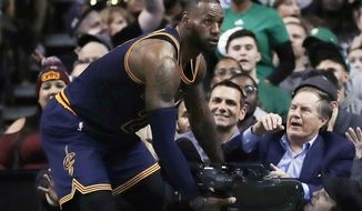 New England Patriots coach Bill Belichick, top right, watches as Cleveland Cavaliers forward LeBron James, left, collides with a televison cameraman during the fourth quarter of an NBA basketball game in Boston, Wednesday, March 1, 2017. The Boston Celtics defeated the Cavaliers 103-99. (AP Photo/Charles Krupa)