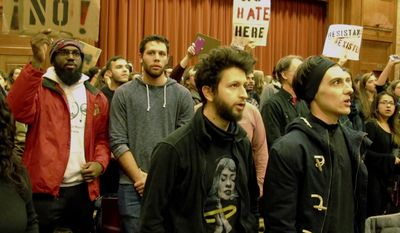 Middlebury College students turn their backs to Charles Murray, unseen, who they call a white nationalist, during his lecture in Middlebury, Vt., Thursday, March 2, 2017. Hundreds of college students on Thursday protested a lecture by a speaker they call a white nationalist, forcing the college to move his talk to an undisclosed campus location from which it was live-streamed to the original venue but couldn't be heard above protesters' chants, feet stamping and occasional smoke alarms. (AP Photo/Lisa Rathke)
