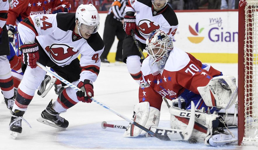 Washington Capitals goalie Braden Holtby (70) stops the puck against New Jersey Devils left wing Miles Wood (44) during the second period of an NHL hockey game, Thursday, March 2, 2017, in Washington. (AP Photo/Nick Wass)