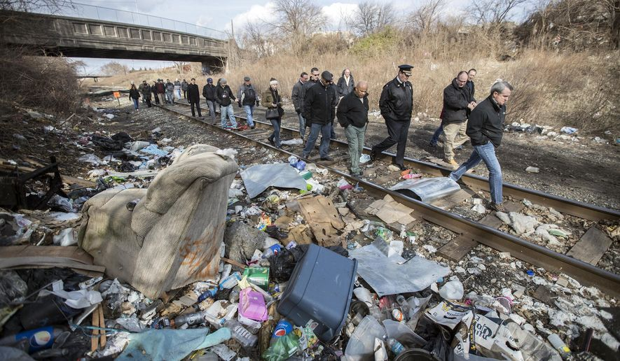 FOR RELEASE SATURDAY, MARCH 4, 2017, AT 3:01 A.M. EST.- This photo taken Feb. 2, 2017, shows a group visits largest open air drug market in the Kensington section of Philadelphia. This open air drug market runs along the Conrail line. Litter and used needles cover the area.  (Michael Bryant/The Philadelphia Inquirer via AP)