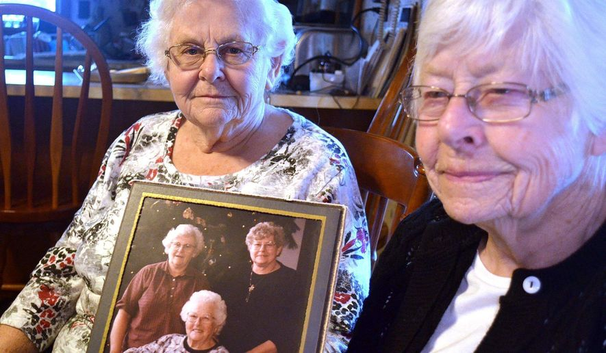 In a Feb. 21, 2017 photo, sisters Susie Armstrong, 83, and Shirley Clark, 88, pose for a photo at Armstrong's home in Stoneboro, Mercer County, Pa., holding a photo of themselves with their mother, Grace Vath, seated. The sisters have been searching for their older brother, who may have been born at the Veil Maternity Hospital in Corry, Pa. in about 1926. (Jim Martin/Erie Times-News via AP)