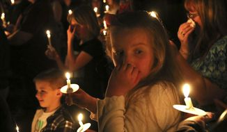 Alyssa Bell, 9, of Riddle, Ore. participates in a candlelight vigil for the victims of a house fire at a Riddle home earlier in the day, Wednesday night, March 1, 2017, in Riddle, Ore. Several children died in a house fire Wednesday in an Oregon timber town and their mother, her husband and a 13-year-old sibling were critically injured, a sheriff's official said. The cause of the blaze did not appear suspicious, but an investigation was continuing, authorities said. (Michael Sullivan/The News-Review via AP)