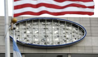 The blue oval Ford Motor Company logo is missing from the south side of the Ford World Headquarters building  in Dearborn, Mich., Thursday, March 2, 2017. According to officials, the blue fabric blew out of its structure and onto the roof due to high winds, Wednesday night. Crews will replace the oval soon. (Todd McInturf /Detroit News via AP)