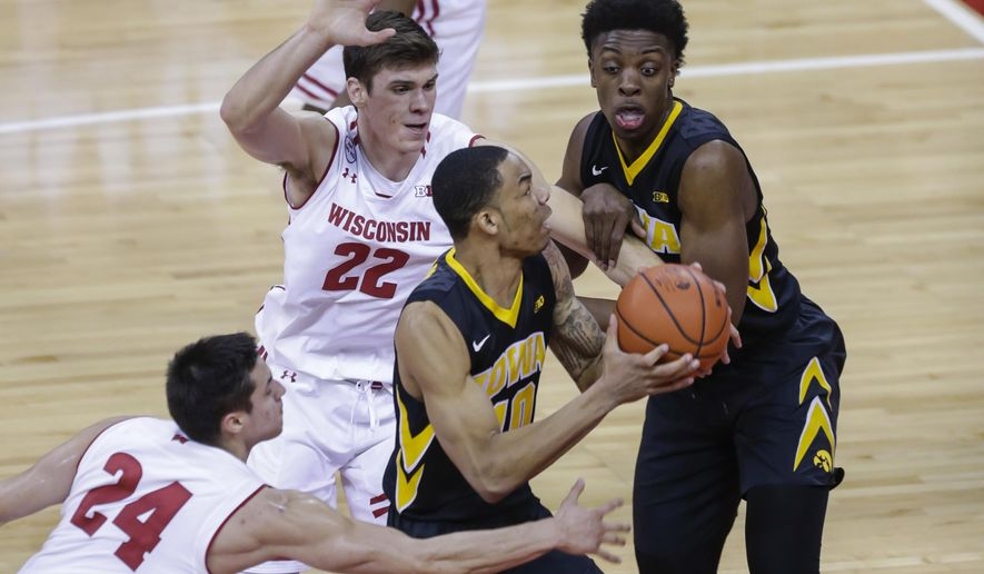 Iowa's Christian Williams (10) prepares to shoot against Wisconsin's Bronson Koenig (24) and Ethan Happ (22) during the first half of an NCAA college basketball game Thursday, March 2, 2017, in Madison, Wis. (AP Photo/Andy Manis)