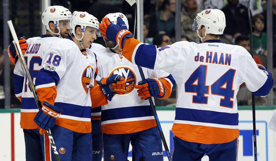 New York Islanders' Ryan Strome (18), Calvin de Haan (44) and Andrew Ladd (16) celebrate a goal by Ladd, with an assist from Strome, during the second period of an NHL hockey game against the Dallas Stars on Thursday, March 2, 2017, in Dallas. (AP Photo/Tony Gutierrez)