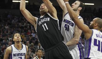 Brooklyn Nets center Brook Lopez (11) drives to the basket against Sacramento Kings defenders Kosta Koufos (41), Arron Afflalo (40) and Skal Labissiere (3) during the first half of an NBA basketball game in Sacramento, Calif., Wednesday, March 1, 2017. (AP Photo/Steve Yeater)