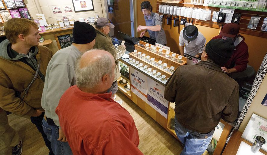 In this Oct. 1, 2015 file photo, employees of Amazon Organics, a pot dispensary in Eugene, Ore., help customers purchase recreational marijuana. Amid concerns of a federal crackdown lawmakers in Oregon are moving to protect the personal information of marijuana customers. (AP Photo/Ryan Kang, File)