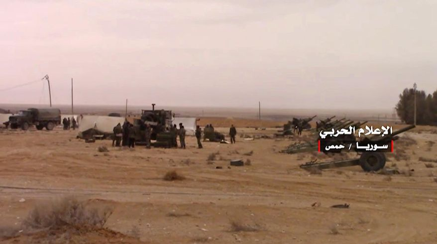 """In this Wednesday, March 1, 2017 frame grab from video provided by the government-controlled Syrian Central Military Media, Syrian forces prepare to fire on an Islamic State group's position, at the ancient city of Palmyra in the central city of Homs, Syria. Syrian state media says government forces have reached the edge of Palmyra and are poised to reclaim the historic town from the Islamic State group. Arabic reads, """"Central Military Media, Homs, Syria."""" (Syrian Central Military Media, via AP)"""
