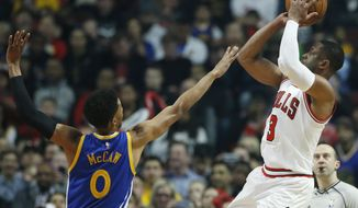 Chicago Bulls guard Dwyane Wade, right, shoots against Golden State Warriors guard Patrick McCaw during the first half of an NBA basketball game Thursday, March 2, 2017, in Chicago. (AP Photo/Nam Y. Huh)