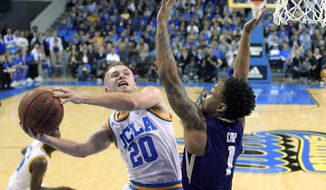 UCLA guard Bryce Alford, left, shoots as Washington guard David Crisp defends during the first half of an NCAA college basketball game, Wednesday, March 1, 2017, in Los Angeles. (AP Photo/Mark J. Terrill)