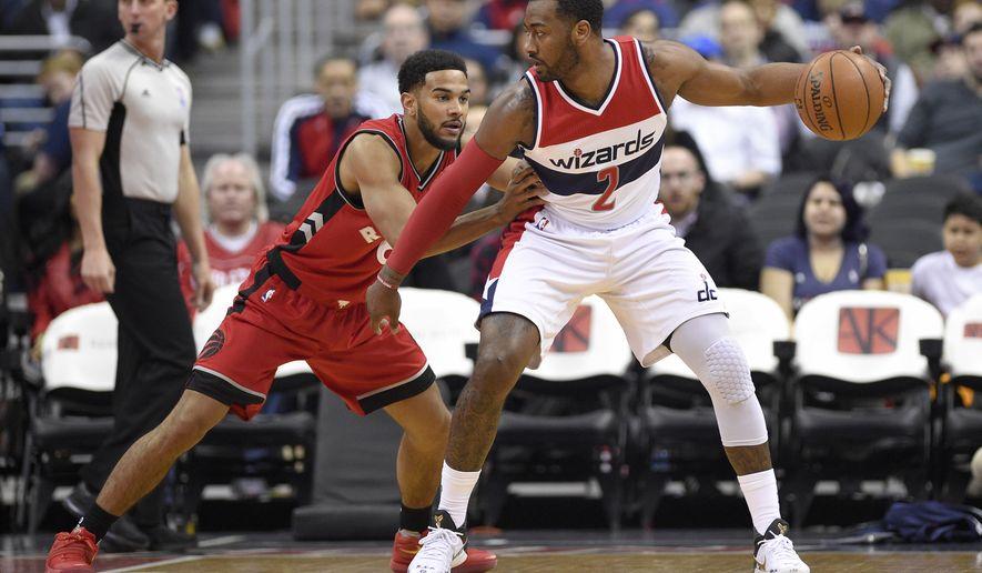 Washington Wizards guard John Wall (2) dribbles next to Toronto Raptors guard Cory Joseph (6) during the first half of an NBA basketball game, Friday, March 3, 2017, in Washington. (AP Photo/Nick Wass)