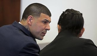 Aaron Hernandez talks with a member of his defense team during his double murder trial in Suffolk Superior Court, Friday, March 3, 2017, in Boston. Hernandez is accused in the killing Daniel de Abreu and Safiro Furtado in Boston's South End, on July 16, 2012. (John Wilcox/The Boston Herald via AP)