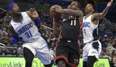 Miami Heat guard Dion Waiters (11) is fouled by Orlando Magic forward Terrence Ross (31) while driving to the basket as Magic guard Elfrid Payton (4) helps defend during the first half of an NBA basketball game, Friday, March 3, 2017, in Orlando, Fla. (AP Photo/Phelan M. Ebenhack)