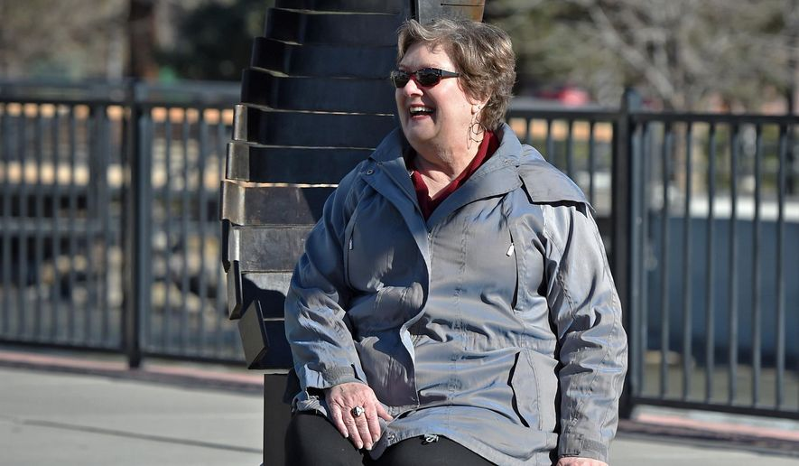This photo taken Feb. 16, 2017, shows Christine Fey sitting on an art piece at Bicentennial Park in Reno, Nev.  Fey retired after nearly 30 years working to promote the arts in Reno, including leading the commission that saw the creation of Artown and the McKinley Arts and Culture Center. (Andy Barron /The Reno Gazette-Journal via AP)