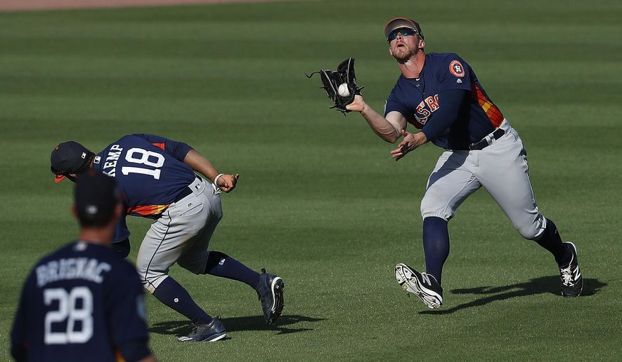 Houston Astros' Jon Kemmer (75) calls off Tony Kemp (18) as he makes a catch on a fly ball off the bat of New York Mets' Phillip Evans in the eighth inning of a spring training baseball game Friday, March 3, 2017, in Port St. Lucie, Fla. New York won 11-3. (AP Photo/John Bazemore)