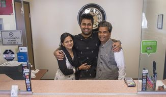 ADVANCE FOR THE WEEKEND OF MARCH 4-5 AND THEREAFTER - In a Feb. 21, 2017 photo, Kunal, Sarita and Ken Sah are reunited again at the hotel they built in 2001 after living some 10 years apart. Kunal's parents, Ken and Sarita Sah, were forced to leave the country in 2006 after losing their legal battle with U.S. Immigration authorities. Kunal has been running the family's hotel business in Green River since 2011, trying to keep his parents' dream alive without them.  (Leah Hogsten/The Salt Lake Tribune via AP)