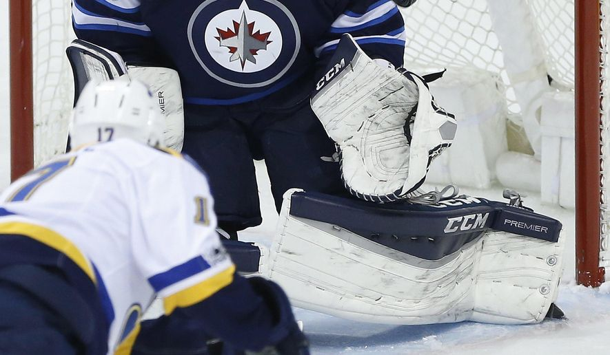 Winnipeg Jets goalie Connor Hellebuyck (37) saves the shot by St. Louis Blues' Jaden Schwartz (17) during the first period of an NHL hockey game Friday, March 3, 2017, in Winnipeg, Manitoba. (John Woods/The Canadian Press via AP)