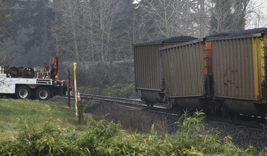 FILE--In this Dec. 28, 2016, file photo, a BNSF coal train heading from Montana to British Columbia sits with one car partially off the track about one mile east of Wintler Park, in Vancouver, Wash. BNSF Railway and seven environmental groups in Washington and Oregon have settled a lawsuit saying that coal spilled from trains pollutes waterways in Washington state.BNSF admits no wrongdoing in the settlement finalized Friday, March 3, 2017. (Ariane Kunze /The Columbian via AP, file)