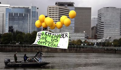 FILE--In this Oct. 3, 2013, file photo, opponents of coal export projects float a message to Oregon Gov. John Kitzhaber over the Willamette River in downtown Portland, Ore. BNSF Railway and seven environmental groups in Washington and Oregon have settled a lawsuit saying that coal spilled from trains polluting the Columbia River and other waterways in the Pacific Northwest. (AP Photo/Don Ryan, file)