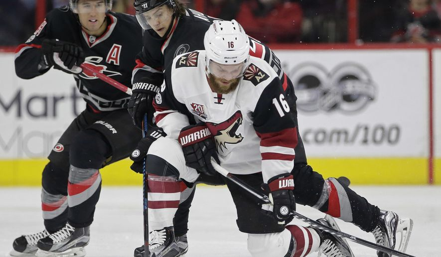 Arizona Coyotes' Max Domi (16) controls the puck as Carolina Hurricanes' Sebastian Aho, of Finland, and Victor Rask (49), of Sweden, pursue during the second period of an NHL hockey game in Raleigh, N.C., Friday, March 3, 2017. (AP Photo/Gerry Broome)