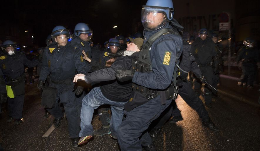 A riot police take away a man as the demonstration marked the 10th anniversary of an eviction that sparked three days of massive riots, in Copenhagen on Wednesday March 1, 2017. Police in Copenhagen say four of the at least nine people arrested overnight will be indicted of violence against officers in connection with the demonstration A handful of the 1,000 participants fired slingshots and threw rocks, fireworks and bottles at helmeted riot police and dozens of shop and bank windows were smashed. (Thomas Borberg/POLFOTO via AP)