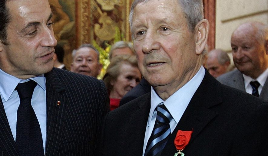FILE - In this March 17, 2008 file photo, then French President Nicolas Sarkozy, left, talks with French former soccer legend Raymond Kopa after he was awarded Officer de la Legion d'Honneur, or Legion of Honor, in Paris.Former France and Real Madrid attacking midfielder Raymond Kopa, the first French player to win the Ballon d'Or, has died. He was 85. (AP Photo/Christophe Ena, Pool, File)