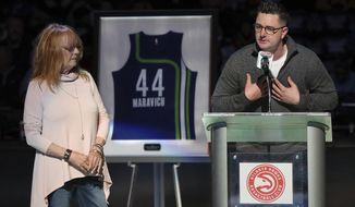 """Pistol"" Pete Maravich's wife, Jackie Maravich, listens as their son Josh speaks while Maravich's No. 44 Atlanta Hawks jersey is retired during halftime of an NBA basketball game between the Hawks and the Cleveland Cavaliers at Philips Arena on Friday, March 3, 2017, in Atlanta. (Curtis Compton/Atlanta Journal-Constitution via AP)"