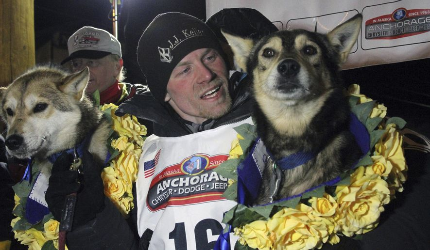 This March 15, 2016, photo shows Dallas Seavey posing with his lead dogs Reef, left, and Tide after finishing the Iditarod Trail Sled Dog Race in Nome, Alaska. Seavey has won four out the last five Idiatrods and will be in this year's race, which starts Saturday, March 4, 2017, in Anchorage, Alaska. (AP Photo/Mark Thiessen)