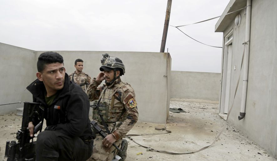 Iraqi special forces take cover on a roof overlooking Islamic State group positions, in the Mamun neighborhood of western Mosul, Iraq, Thursday, March 2, 2017. Iraqi forces have retaken a handful of neighborhoods on Mosul's southwestern edge since launching the operation to retake the city's western half last month, but IS fighters continued to launch fierce counterattacks on Iraqi positions inside Mosul. (AP Photo/Susannah George)