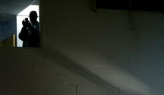 A man looks out a window as U.S. Sen. Bob Menendez delivers remarks in a gymnasium at the Kaplen Jewish Community Center on the Palisades during a rally against recent bomb threats made to jewish centers, Friday, March 3, 2017, in Tenafly, N.J. (AP Photo/Julio Cortez)