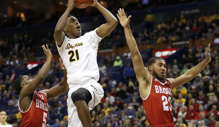 Wichita State's Darral Willis Jr. (21) heads to the basket as Bradley's Darrell Brown, left, and Dwayne Lautier-Ogunleye defend during the second half of an NCAA college basketball game in the quarterfinals of the Missouri Valley Conference men's tournament Friday, March 3, 2017, in St. Louis. (AP Photo/Jeff Roberson)