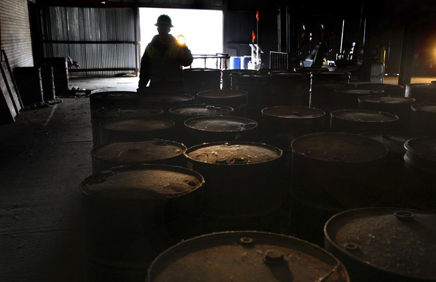 Brian Kelly with the EPA uses a flash light to show barrels of chemicals that have been collected for classification and removal from around the former Rock Tenn paper mill site on Helen Avenue in Otsego, Mich.   (Mark Bugnaski/Kalamazoo Gazette-MLive Media Group via AP)