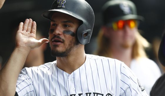 FILE - In this Sept. 21, 2016, file photo, Colorado Rockies' Nolan Arenado is congratulated by teammates after scoring on a homer by Tom Murphy off St. Louis Cardinals relief pitcher Jonathan Broxton during a baseball game in Denver. Arenado is hoping to match his output from last season when he led the majors in RBIs and tied for the lead in home runs in the National League. (AP Photo/David Zalubowski, File)