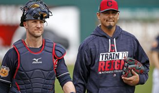 Cleveland Indians starting pitcher Carlos Carrasco, right, walks in from the bullpen with catcher Yan Gomes, left, after warming up for a spring training baseball game against the Colorado Rockies, Friday, March 3, 2017, in Goodyear, Ariz. (AP Photo/Ross D. Franklin)