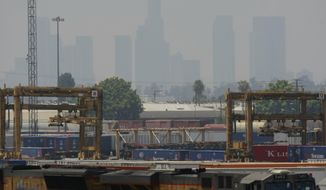 FILE - In this June 24, 2010 file photo, the Los Angeles skyline is seen above the Union Pacific Railroad East Los Angeles Intermodal facility in the City of in Commerce, Calif. A long-term plan for cleaning up the air in a huge swath of smoggy Southern California is due for consideration by regulators. Directors of the South Coast Air Quality Management District are expected to vote on the plan Friday, March 3, 2017. (AP Photo/Damian Dovarganes, File)