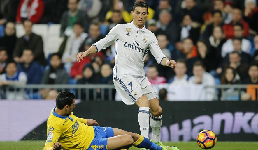 Real Madrid's Cristiano Ronaldo, right, is tackled by Las Palmas Vicente Gomez during a Spanish La Liga soccer match between Real Madrid and Las Palmas at the Santiago Bernabeu stadium in Madrid, Spain, Wednesday March 1, 2017. (AP Photo/Paul White)