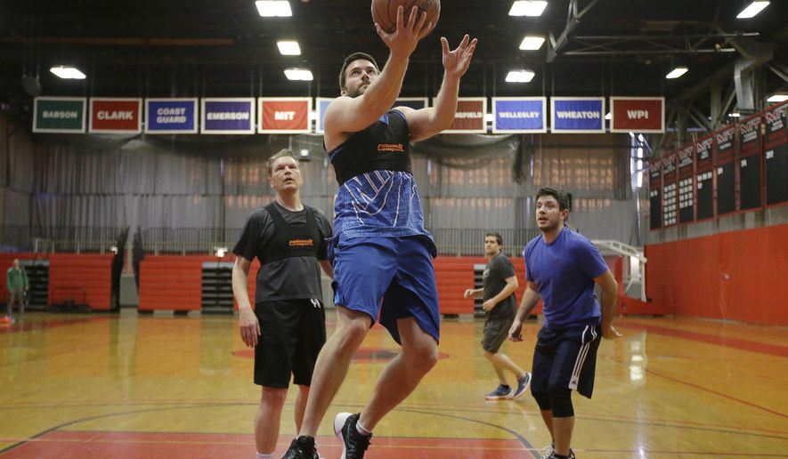Jeremias Engelmann drives toward the hoop wearing a Catapult monitoring system compression vest while playing basketball  Friday, March 3, 2017, in Cambridge, Mass. Athlete trackers are being used by hundreds of teams in dozens of sports helping coaches plan their practices, make substitutions in games and decide when a player is ready to return from an injury by accumulating biometric and positioning data collected from the trackers. (AP Photo/Stephan Savoia)