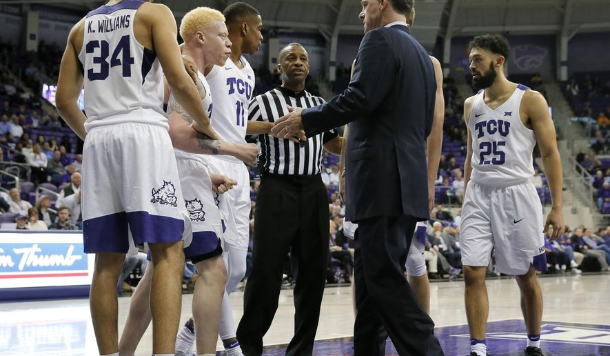 In this March 1, 2017 photo, TCU's Kenrich Williams (34), Jaylen Fisher (0), Brandon Parrish (11) and Alex Robinson (25) talk with an official and head coach Jamie Dixon, center right, after a foul call during an NCAA college basketball game against Kansas State in Fort Worth, Texas. A week into February, TCU had just pulled out a one-point victory at home and had already won six Big 12 games under new coach Jamie Dixon. (AP Photo/Tony Gutierrez)