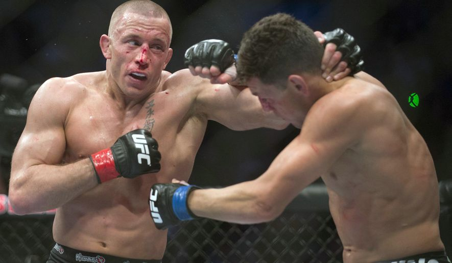 FILE - In this March 16, 2013, file photo, Georges St. Pierre, left, lands a blow to Nick Diaz, from the United States, during their UFC 158 welterweight mixed martial arts title fight in Montreal. Although St. Pierre has been out of the UFC for 3 1/2 years, the Canadian is still one of the biggest names in MMA. The longtime welterweight champ's comeback fight later this year will be for Michael Bisping's middleweight belt. (Graham Hughes/The Canadian Press via AP, File)