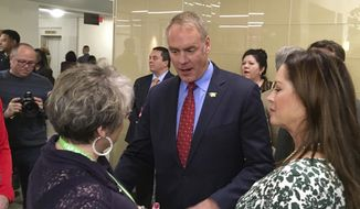 Newly sworn-in Interior Secretary Ryan Zinke, and his wife Lola, right, greets an Interior Department employee on the Interior Department's 168th birthday, Friday, March 3, 2017, at the Interior Department in Washington. (AP Photo/Matthew Daly) ** FILE **