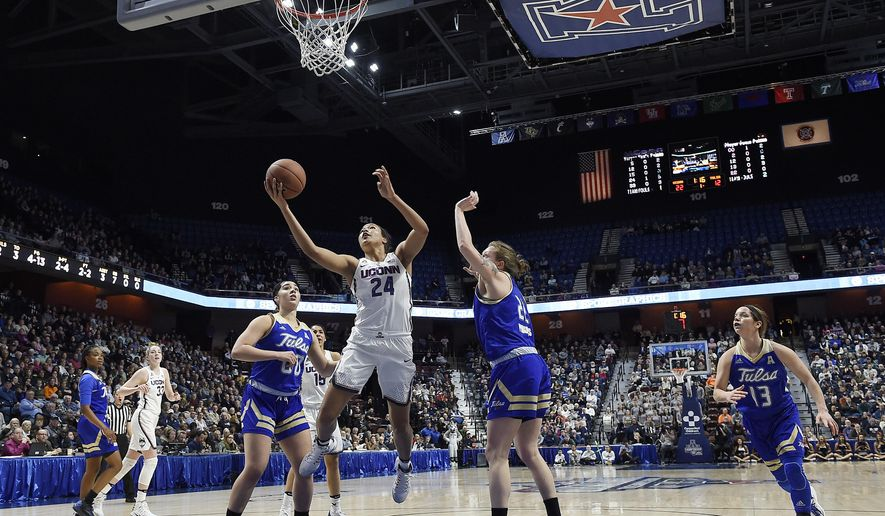 Connecticut's Napheesa Collier, center, splits the defense of Tulsa's Kendrian Elliott, left, and Jessica Pongonis, right, during the first half of an NCAA college basketball game in the American Athletic Conference tournament quarterfinals at Mohegan Sun Arena, Saturday, March 4, 2017, in Uncasville, Conn. (AP Photo/Jessica Hill)
