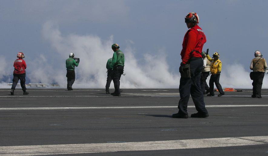 With smoke created by a F18 fighter jet taking off crewmen prepare the next one aboard the U.S. Navy aircraft carrier USS Carl Vinson (CVN 70) off the disputed South China Sea Friday, March 3, 2017. The U.S. military took journalists Friday to the carrier on routine patrol off the disputed South China Sea, sending a signal to China and American allies of its resolve to ensure freedom of navigation and overflight in one of the world's security hotspots.(AP Photo/Bullit Marquez)