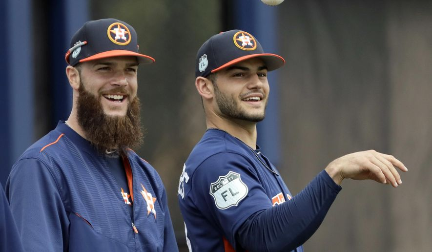FILE - In this Sunday, Feb. 19, 2017, file photo, Houston Astros' Lance McCullers, right, tosses a ball as he waits with Dallas Keuchel during a spring training baseball workout in West Palm Beach, Fla. The pressure is on for McCullers and 2015 Cy Young Award winner Dallas Keuchel at the top of the Astros rotation heading into a season of high expectations for the team. (AP Photo/David J. Phillip, File)