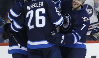Winnipeg Jets' Nikolaj Ehlers (27), Blake Wheeler (26) and Ben Chiarot (7) celebrate Chiarot's goal against the Colorado Avalanche during second period NHL hockey action in Winnipeg, Manitoba, Saturday, March 4, 2017. (John Woods/The Canadian Press via AP)