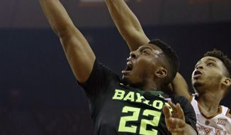 Baylor guard King McClure (22) shoots against Texas guard Eric Davis, Jr. (10) during the first half of an NCAA college basketball game, Saturday, March 4, 2017, in Austin, Texas. (AP Photo/Michael Thomas)