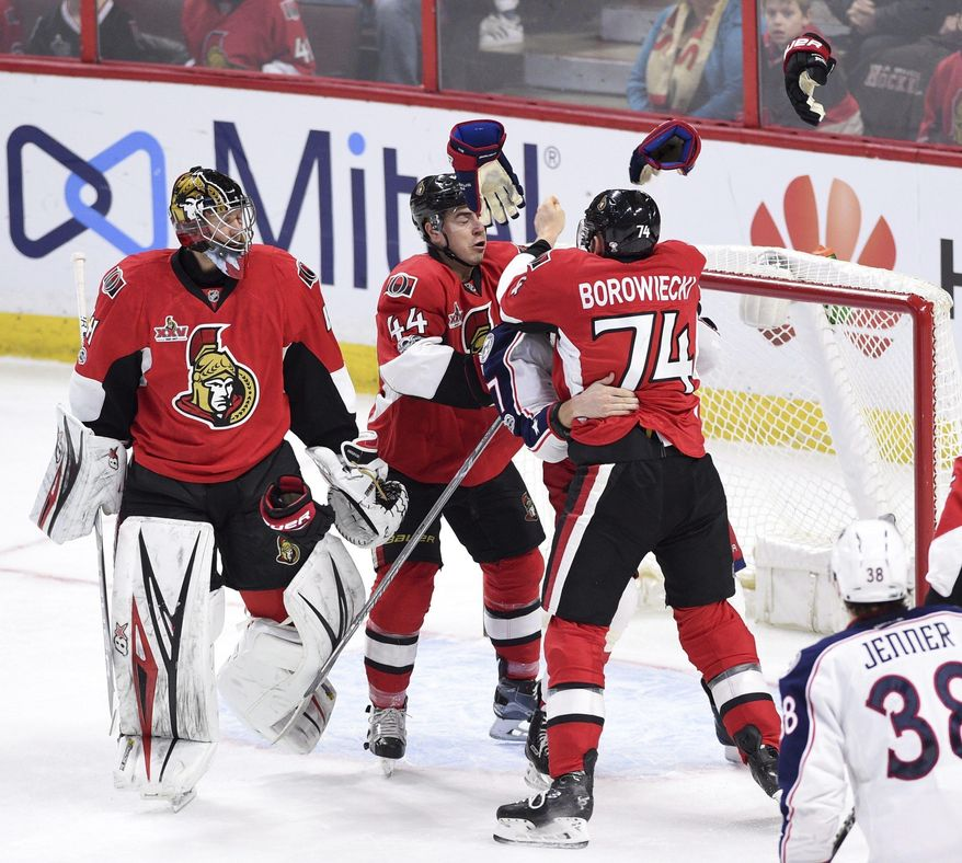 Gloves fly off as Ottawa Senators defenseman Mark Borowiecki (74) and Columbus Blue Jackets center Brandon Dubinsky (17) tussle during the first period of an NHL hockey game in Ottawa, Ontario, Saturday, March 4, 2017. Senators goalie Craig Anderson, left, and center Jean-Gabriel Pageau (44) watch. (Sean Kilpatrick/The Canadian Press via AP)